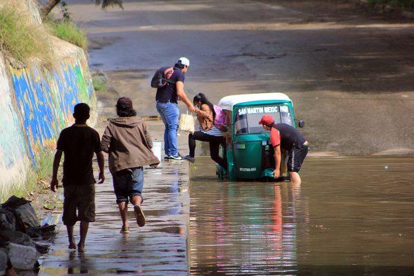 Mototaxi intenta cruzar un puente inundado