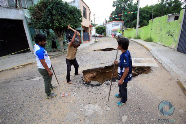 Vecinos deciden quitar el asfalto que quedó sobrepuesto tras el hundimiento de la tierra.